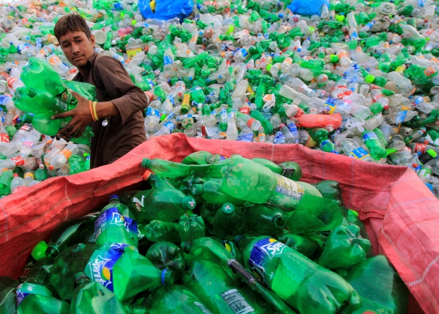 A worker sorts bottles to throw them in a plastic bottle chipper at a recycling workshop in Islamabad
